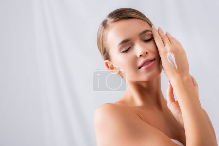 sensual young woman with closed eyes and cream on hand on white