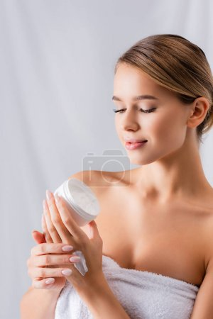 young woman with bare shoulders holding jar with face cream on white