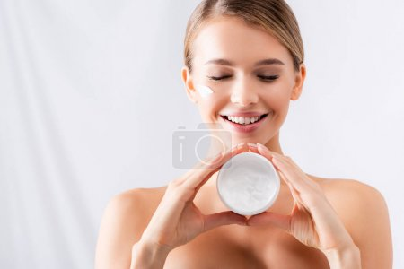 smiling young woman with closed eyes and cream on face holding jar on white