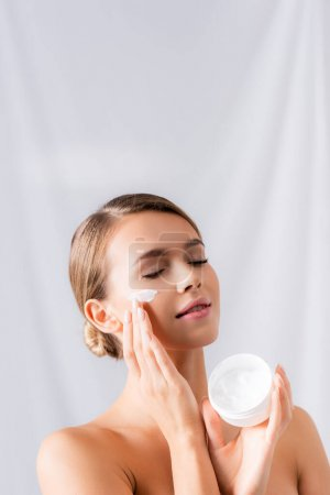 junge Frau mit nackten Schultern, die Glas hält und Gesichtscreme auf Weiß aufträgt