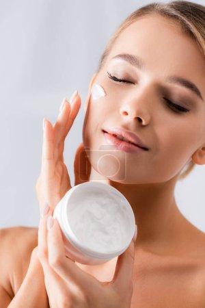 Frau mit nackten Schultern hält Glas und trägt Gesichtscreme auf