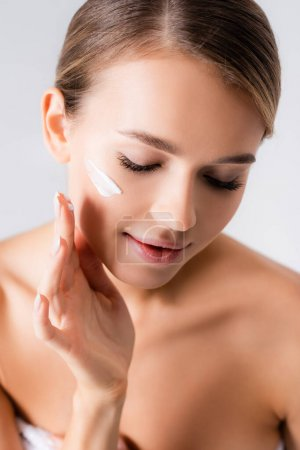 young woman with bare shoulders applying face cream isolated on white