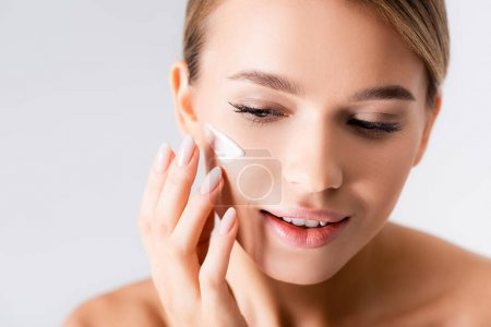 young woman with bare shoulders applying moisturizing cream on face isolated on white