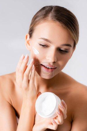 junge Frau mit nackten Schultern, die Glas hält und Gesichtscreme isoliert auf weiß aufträgt