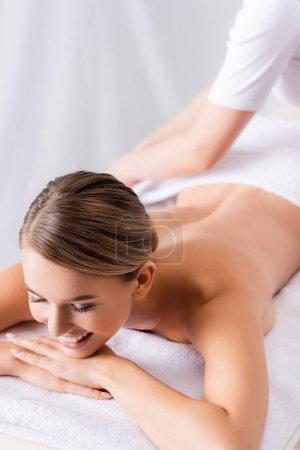 masajista borrosa ajustando toalla en cliente feliz acostado en mesa de masaje