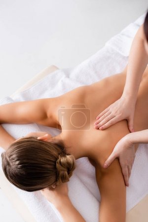 high angle view of masseur massaging woman on massage table