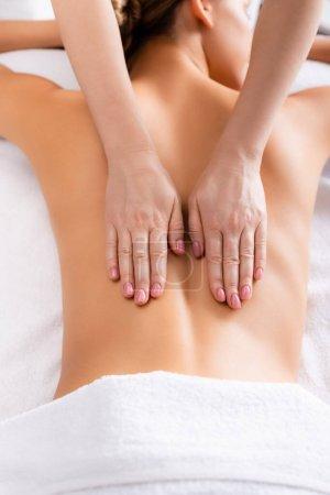 vista recortada de masajista cliente de masaje acostado en la mesa de masaje
