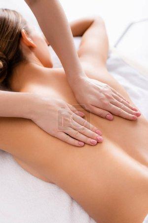 masajista masaje joven cliente acostado en mesa de masaje