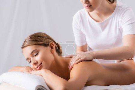 masajista mujer masaje complacido cliente acostado en mesa de masaje
