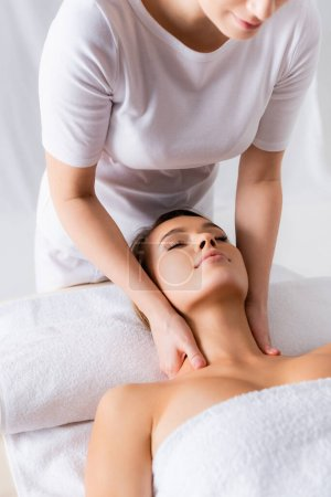 female masseur doing neck massage to pleased client in spa salon