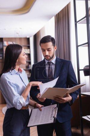 Photo pour Femme d'affaires détenant un contrat et pointant vers les papiers près partenaire d'affaires musulman - image libre de droit