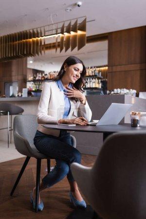 Photo pour Heureux freelance toucher la poitrine tout en regardant ordinateur portable au restaurant, flou au premier plan - image libre de droit