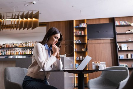 Photo for Positive freelancer looking at laptop while sitting in restaurant - Royalty Free Image