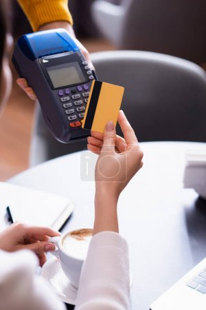 partial view of woman holding credit card near credit card reader in hand of waiter