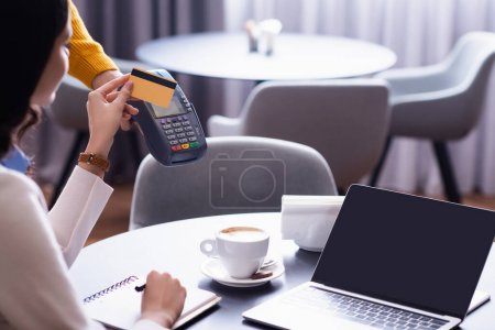 cropped view of freelancer holding credit card near credit card reader in hand of waiter