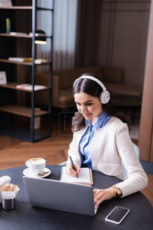 young freelancer in headphone writing in notebook near laptop in restaurant