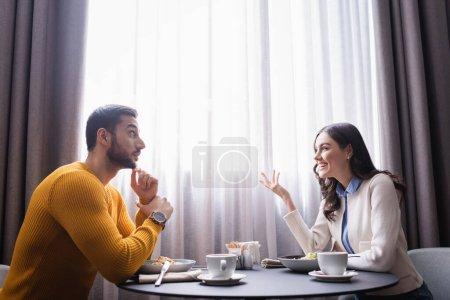 Photo pour Femme souriante parlant au petit ami arabe près de la nourriture et du café dans le restaurant - image libre de droit