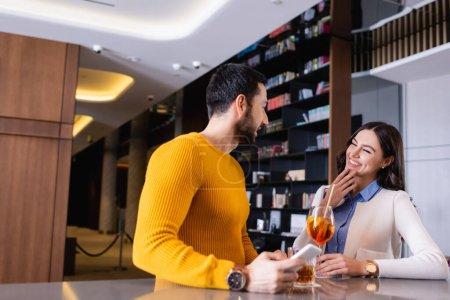 Photo pour Femme gaie debout près d'un ami arabe avec smartphone et boissons sur le comptoir du bar - image libre de droit