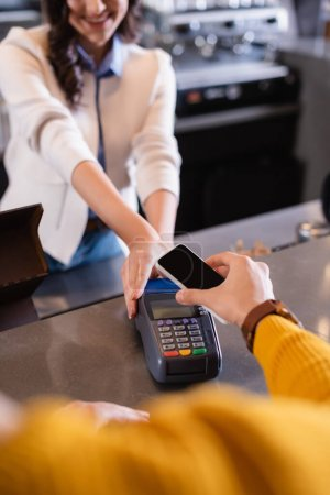Cropped view of man paying with smartphone near barman with payment terminal in restaurant
