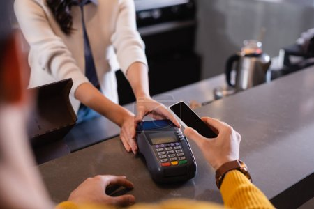 Cropped view of man paying with smartphone near payment terminal in restaurant