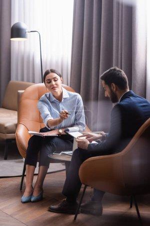 Photo pour Jeune femme d'affaires pointant vers presse-papiers près d'un homme d'affaires musulman lors d'une réunion dans un restaurant - image libre de droit