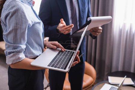 Foto de Vista recortada de la mujer de negocios utilizando el ordenador portátil cerca de la pareja con portapapeles sobre fondo borroso - Imagen libre de derechos