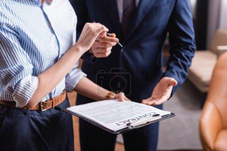 Photo pour Vue recadrée de femme d'affaires détenant contrat près de l'homme d'affaires sur fond flou dans le restaurant - image libre de droit