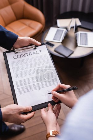 Vue recadrée d'une femme d'affaires signant un contrat près d'un homme d'affaires au restaurant