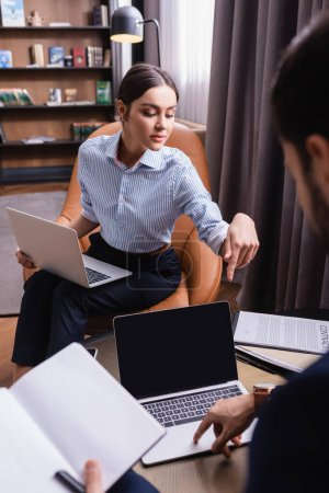 Businesswoman pointing at laptop near colleague with notebook on blurred foreground