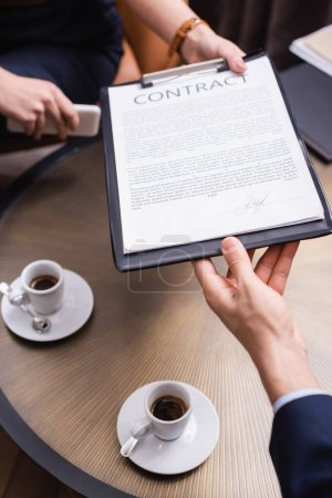 Cropped view of businessman taking contract from businesswoman near coffee in restaurant