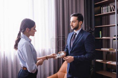 Photo pour Arabe homme d'affaires donnant de l'argent à partenaire dans un restaurant moderne - image libre de droit