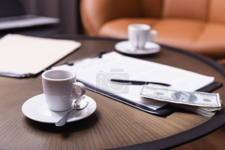 Photo pour Tasse de café près de dollars et presse-papiers sur fond flou sur la table - image libre de droit