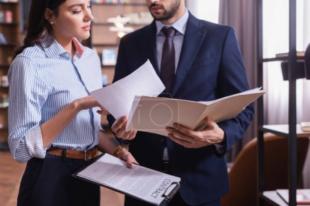 Businessman holding paper folder near colleague with contract in restaurant