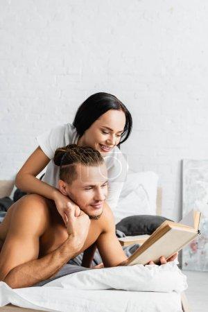 Mujer sonriente abrazando novio sin camisa con libro en la cama