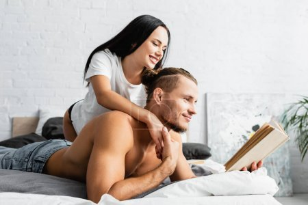 Photo for Smiling woman hugging muscular boyfriend reading book on bed - Royalty Free Image