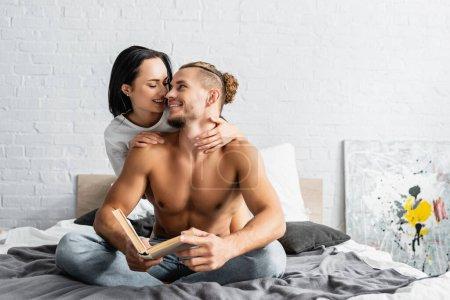 Mujer morena abrazando a hombre sexy con libro en el dormitorio