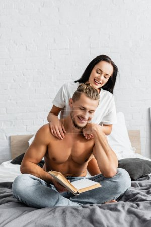 Photo for Young woman hugging muscular boyfriend reading book in bedroom - Royalty Free Image