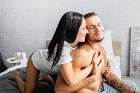 Smiling woman touching sexy boyfriend in bedroom