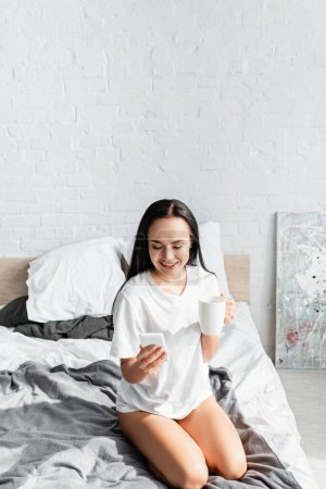 Photo pour Femme gaie avec tasse en utilisant un smartphone sur le lit - image libre de droit
