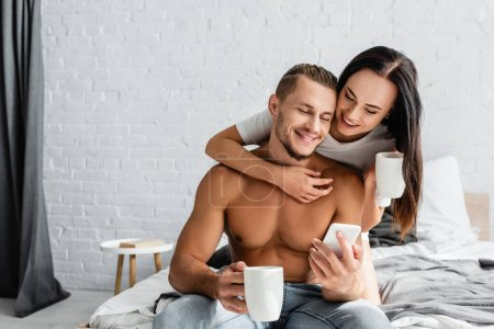 Photo for Shirtless man using smartphone near girlfriend with cup on bed - Royalty Free Image