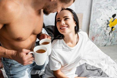 Foto de Mujer sonriente mirando al novio sin camisa con té en la cama - Imagen libre de derechos