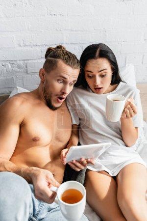 Erstauntes Paar mit Tee mit digitalem Tablet auf dem Bett
