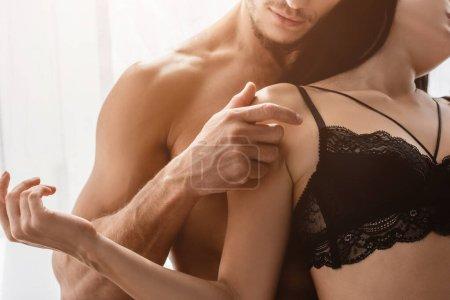 Photo pour Vue recadrée de l'homme torse nu touchant épaule de petite amie en soutien-gorge en dentelle - image libre de droit