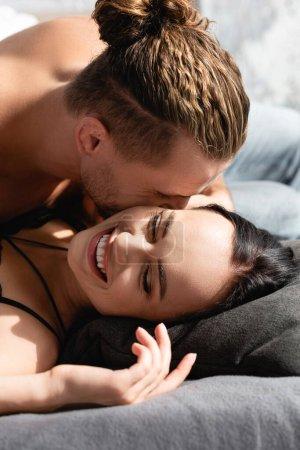 Photo pour Jeune homme embrassant petite amie gaie sur le lit - image libre de droit