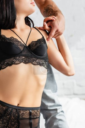 Photo for Cropped view of sexy lingerie on young woman holding boyfriend hand - Royalty Free Image