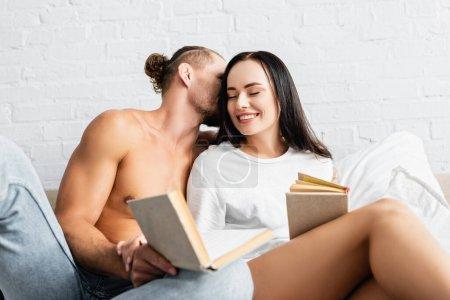 Photo pour Homme sexy embrasser petite amie souriante avec livre sur le premier plan flou - image libre de droit