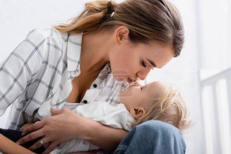 Photo pour Jeune mère les yeux fermés tenant et embrassant son fils à la maison - image libre de droit