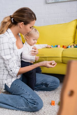 mother giving toy cube to son while playing on floor on blurred foreground
