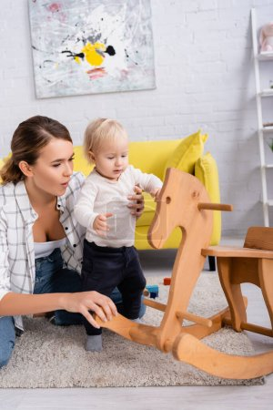 young mother supporting child near rocking horse at home