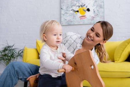 Photo pour Femme souriante regardant enfant équitation cheval à bascule à la maison - image libre de droit